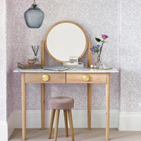 Pared-back dressing room with patterned wallpaper and wooden furniture