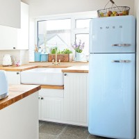 Small white kitchen with retro blue fridge