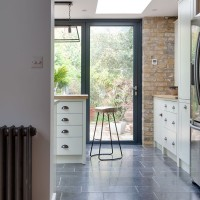 Urban white kitchen with exposed brickwork and modern glazed doors