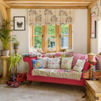 Country living room with candy pink sofa and mix-and-match cushions
