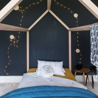 Midnight black bedroom with house-themed bed and fairy lights