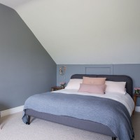 Modern grey attic bedroom with blush pink accents