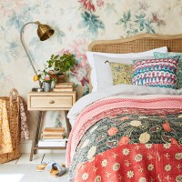 Cosy country bedroom with layered patterned bedcovers