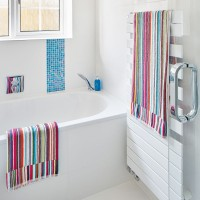 White bathroom with colourful striped towels