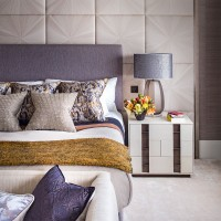 Neutral bedroom with textured wall panel and soft furnishings