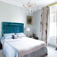 Pale blue bedroom with luxe velvet headboard