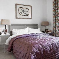 Traditional bedroom with luxurious purple quilt