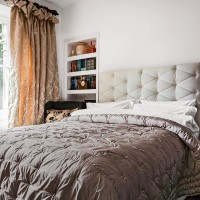 Cosy country bedroom with upholstered bed