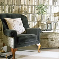 Cosy living room corner with library wallpaper