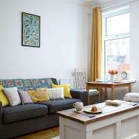 Small white living room with yellow accessories