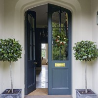 Traditional entrance with gothic-inspired door and marble floor