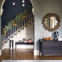 Sage green damask hallway with parquet flooring and festive bannister