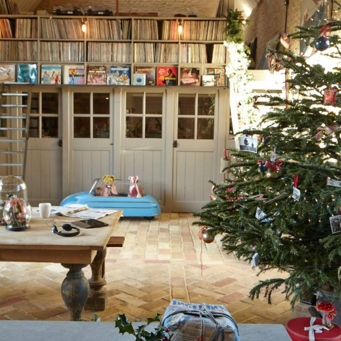 Converted barn living room with mezzanine level and large Christmas tree