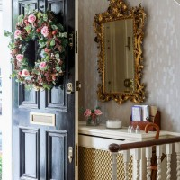 Traditional hallway with black front door and floral wreath