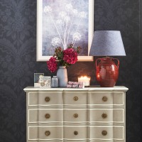 Christmas bedroom with wooden drawers and red